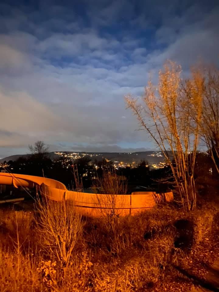 Auf dem Foto ist eine Freibadrutsche zu sehen am Abend und im Hintergrund sind die Lichter der Standt.